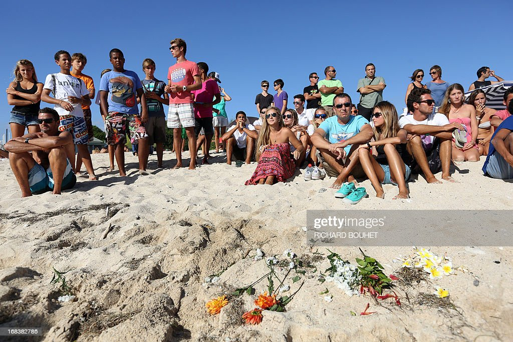 People sit on the beach where others have placed flowers in the sand on the beach of Brisants in Saint-Gilles-les Bains on May 9, 2013 to pay tribute to a surfer killed after he was attacked by a shark on May 8. The 36-year-old French honeymooner was in the sea off the popular beach of Brisants de Saint-Gilles when a shark charged at him twice, prompting a nearby swimmer to raise the alert when he saw blood on the water, the local prefecture said. AFP PHOTO / RICHARD BOUHET