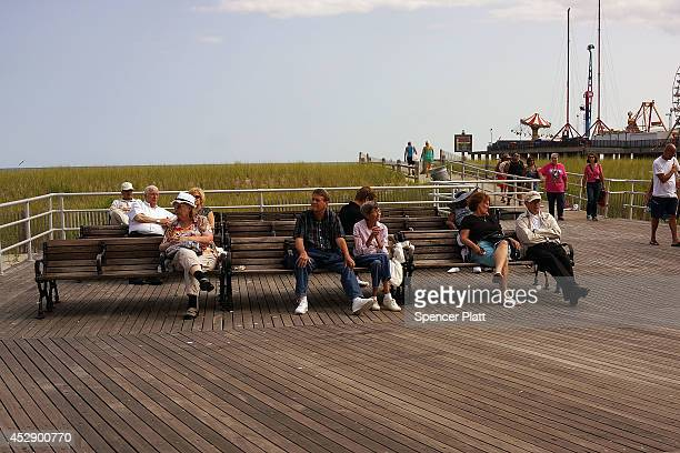 People sit on the boardwalk in Atlantic City on July 29 2014 in Atlantic City New Jersey Since January of 2014 four of Atlantic City's 11 casinos...