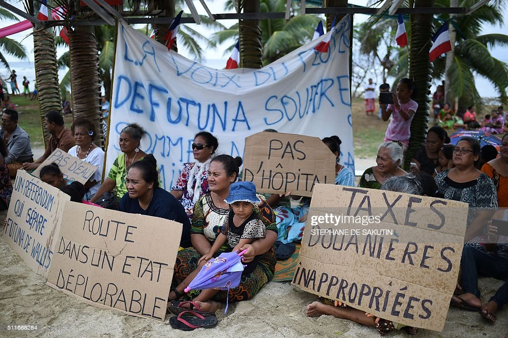People sit on the floor holding banners reading 'Roads in a sorry state' 'Unsiutable custom taxes' and 'No hospital' during a ceremony by 'la grande...