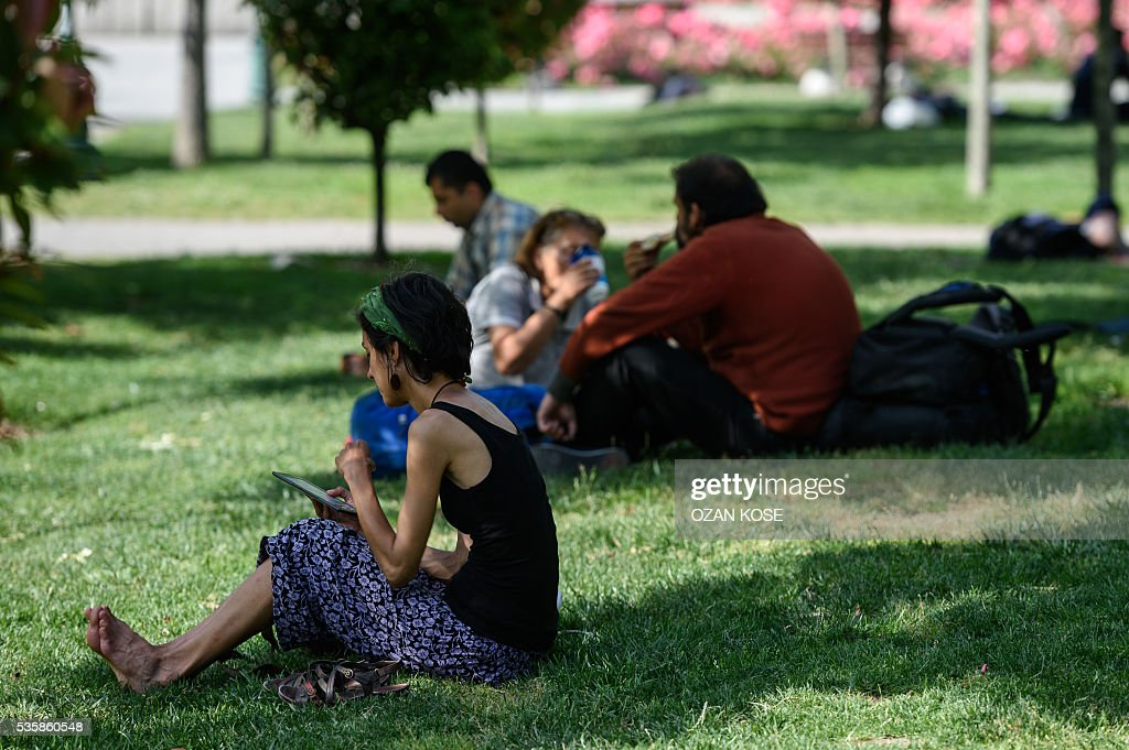 People sit on the grass at the Gezi Park on May 30, 2016 in Istanbul on the eve of the 3rd anniversary of the so-called Gezi Park protests. / AFP / OZAN