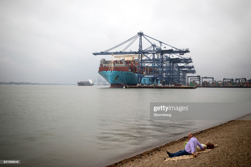 People sit on the shoreline as the Maersk Madrid container ship, operated by A.P. Moller-Maersk A/S, sits docked at the Port of Felixstowe Ltd., a subsidiary of CK Hutchison Holdings Ltd. in Felixstowe, U.K., on Tuesday, Aug. 22, 2017. U.K. exporters are still reaping the benefits of a weaker pound, but they're not sure how long the boost will continue as the country gets closer to withdrawing from the European Union. Photographer: Simon Dawson/Bloomberg via Getty Images