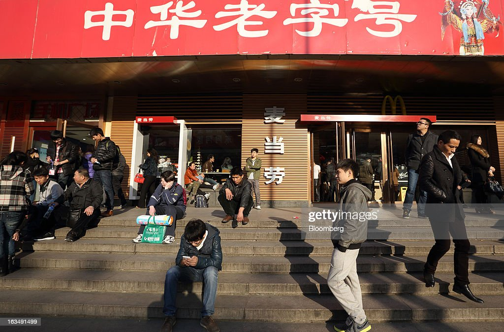People sit on the stairs in front of a McDonald's Corp. restaurant in the Wangfujing shopping district of Beijing, China, on Sunday, March 10, 2013. China's industrial output had the weakest start to a year since 2009 and lending and retail sales growth slowed, toughening challenges for a new leadership that wants to narrow the gap between rich and poor. Photographer: Tomohiro Ohsumi/Bloomberg via Getty Images