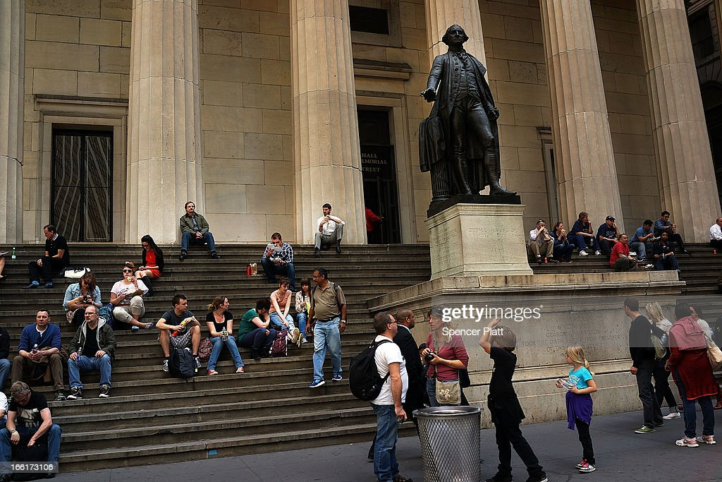 People sit on the steps of Federal Hall next to a statue of George Washington on Wall Street in lower Manhattan during warm weather on April 9, 2013 in New York City. For the first time since October, temperatures are expected to rise above 70 degrees this week in New York and surrounding areas.