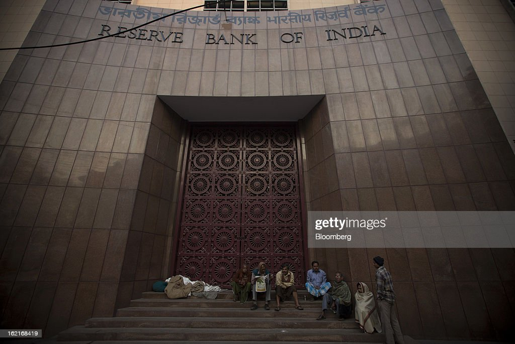 People sit on the steps of the Reserve Bank of India (RBI) in the BBD Bagh area of Kolkata, India, on Tuesday, Feb. 19, 2013. India's slowest economic expansion in a decade is limiting profit growth at the biggest companies even as foreigners remain net buyers of the nation's stocks, according to Kotak Institutional Equities. Photographer: Brent Lewin/Bloomberg via Getty Images
