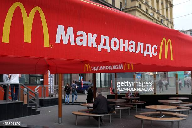 People sit on the terrace of a closed McDonald's restaurant the first to be opened in the Soviet Union in 1990 in Moscow on August 21 2014 Russian...