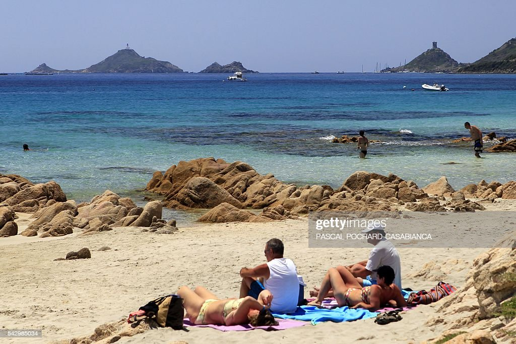People sit on the Terre Sacree beach in Ajaccio on June 25, 2016 on the French island of Corsica. / AFP / PASCAL