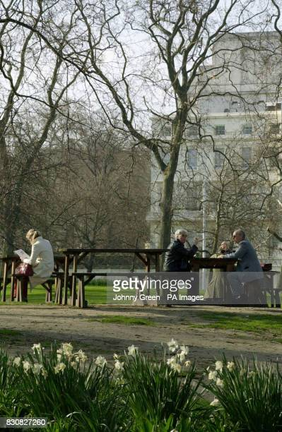 People sit out by picnictables in Green Park in central London to enjoy the Spring sunshine