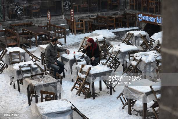 People sit out in the snow at a coffee shop as they drink hot tea in the center of the Kurdishmajority city of Diyarbakir in the southeast of Turkey...