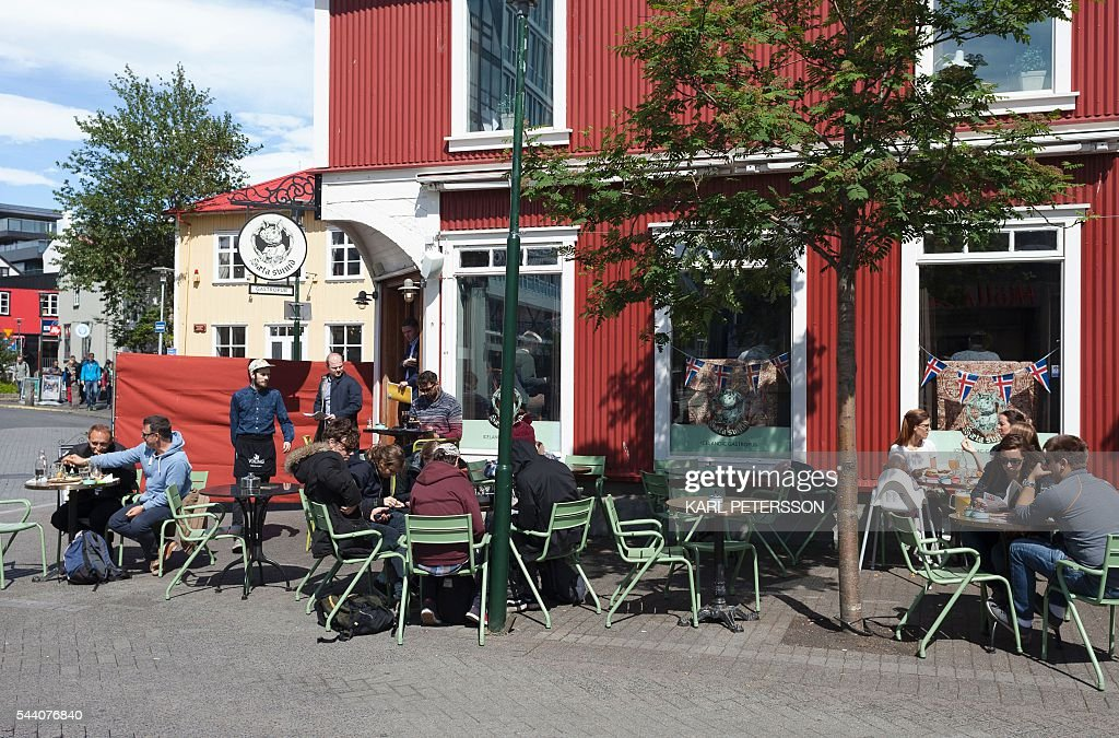 People sit outside a cafe in Reykjavik, on July 1, 2016. With a large part of its population in France for the Euro 2016, Iceland has pretty much come to a standstill these days, except for its tourism sector which is booming. / AFP / Karl Petersson / TO