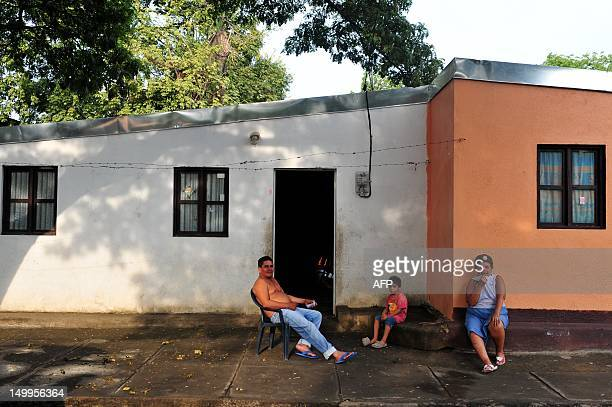 People sit outside of a house in the neighborhood San Sebastian Managua on August 7 2012 AFP PHOTO/Hector RETAMAL