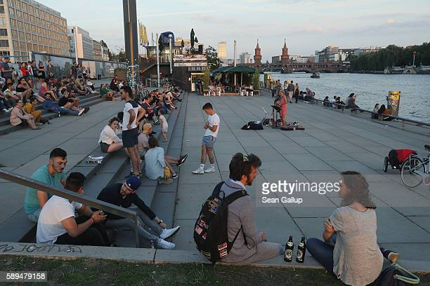 People sit outside on a warm summer evening at the bank of the Spree river near the East Side Gallery remnants of the Berlin Wall on August 13 2016...