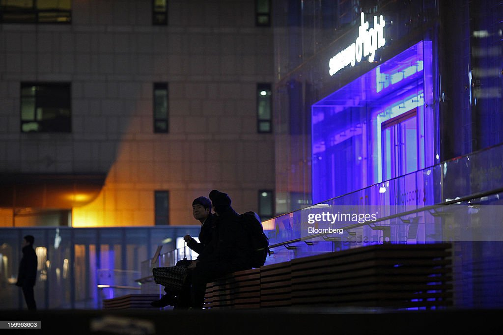 People sit outside the entrance to Samsung Electronics Co.'s Samsung d'light showroom and store in Seoul, South Korea, on Wednesday, Jan. 23, 2013. Samsung, in a preliminary statement of results on Jan. 8, reported an 89 percent jump in profit in the three months ended in December, boosted by its Galaxy line of smartphones. Photographer: Woohae Cho/Bloomberg via Getty Images