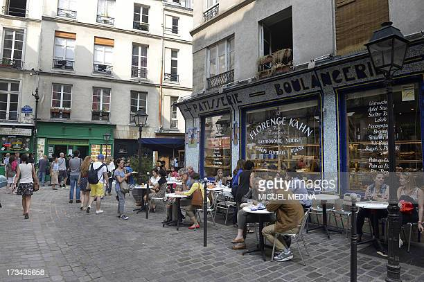 People sit outside the 'Florence Kahn' pastries shop on July 12 2013 in the Rue des Rosiers the Jewish area of the Marais district in Paris AFP PHOTO...
