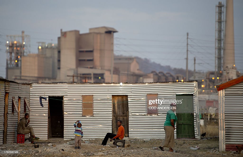 People sit outside their shacks on July 9, 2013 in the Nkaneng shantytown next to the platinum mine, run by British company Lonmin, in Marikana. On August 16, 2012, police at the Marikana mine open fire on striking workers, killing 34 and injuring 78, during a strike was for better wages and living conditions. Miners still live in dire conditions despite a small wage increase.
