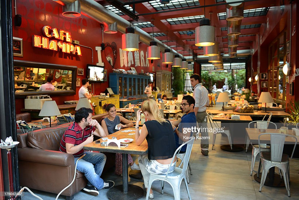 People sit playing cards and smoking Shisha (waterpipe) in Cafe Hamra in Hamra street on July 17, 2013 in Beirut, Lebanon.