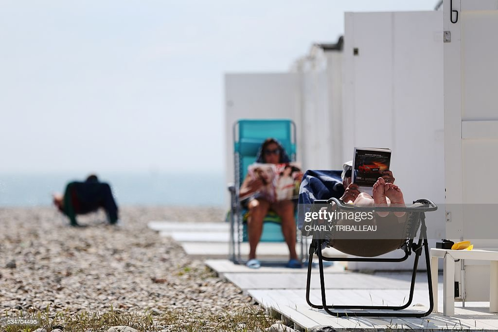 People sit reading on the beach on a sunny day in Le Havre, northwestern France, on May 27, 2016. / AFP / CHARLY