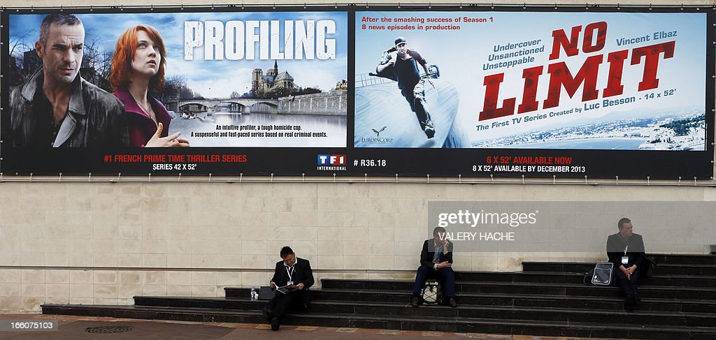People sit under movie posters near the entrance of the MIPTV, one of the world's largest broadcasting and audio-visual trade show, on April 8, 2013 in Cannes, southeastern France. AFP PHOTO / VALERY HACHE