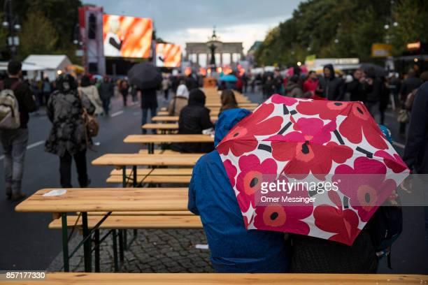 People sit under open umbrellas at an amusement area set up along 17th of June Street in Tiergraten Park near the Brandenburg Gate on German Unity...
