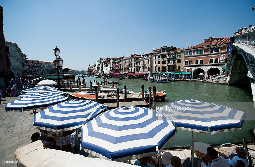 People sit under open umbrellas near Rialto Bridge on June 21, 2012 in Venice, Italy. An intense heatwave is sweeping across many regions in Italy, prompting the country's health ministry to issue a number of high level alerts.