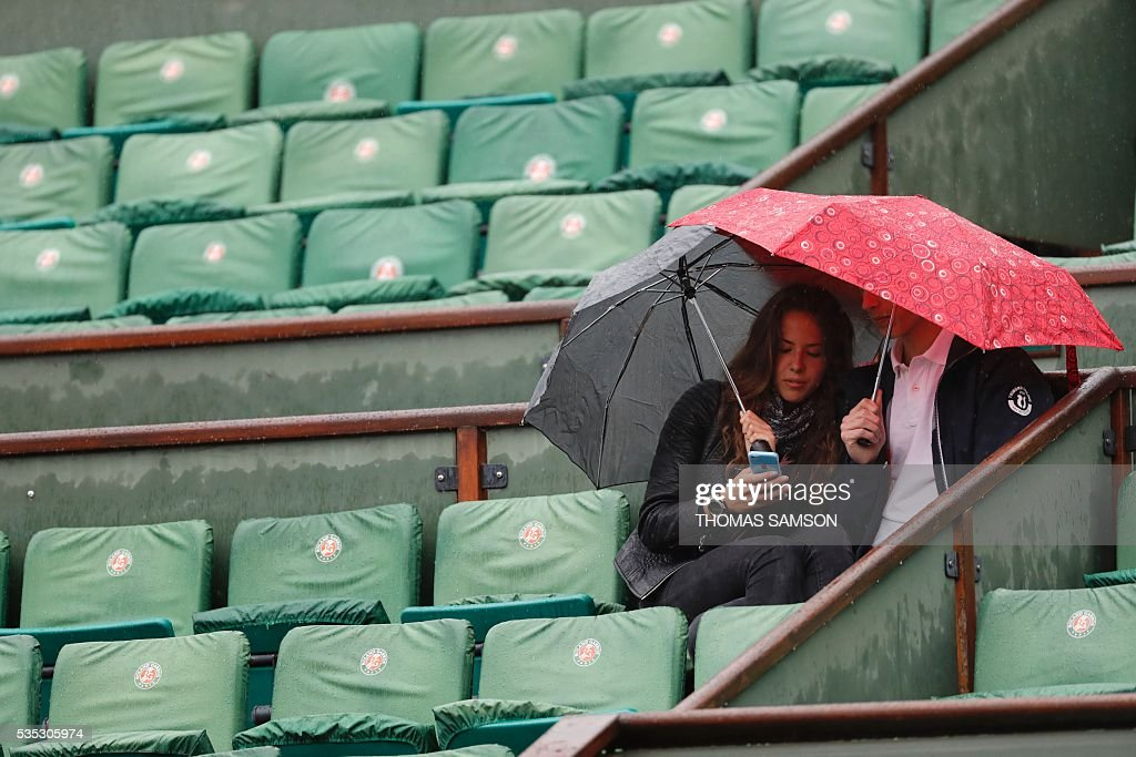 People sit under umbrellas as rain interrupts play during the men's fourth round match between Japan's Kei Nishikori and France's Richard Gasquet at the Roland Garros 2016 French Tennis Open in Paris on May 29, 2016. / AFP / Thomas SAMSON