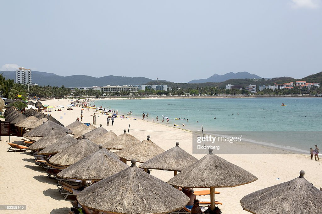 People sit under umbrellas on the beach in the Dadonghai district of Sanya, Hainan Province, China, on Monday, April 7, 2014. The yuan is poised to recover from declines that have made it Asia's worst-performing currency as China seeks to prevent an exodus of capital that would threaten economic growth, according to the most accurate forecasters. Photographer: Brent Lewin/Bloomberg via Getty Images