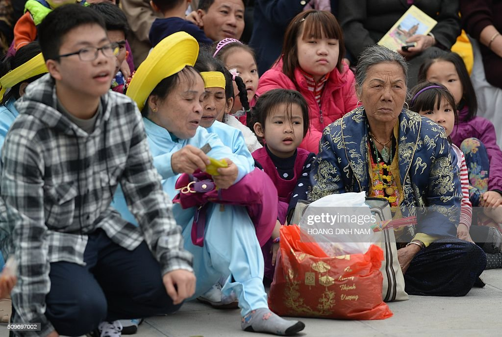 People sit watching da performance during a ceremony marking the 227th anniversary of the Vietnam's Dong Da-Ngoc Hoi victory over China's Qing dynasty's troops in 1789 at a memorial monument to Vietnamese King Quang Trung (1788-1792), winner of the war, in Hanoi on February 12, 2016. AFP PHOTO / HOANG DINH Nam / AFP / HOANG DINH NAM
