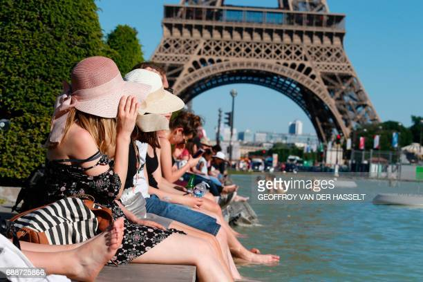 People sit with their feet in the water of the Fountain of Warsaw at the Gardens of the Trocadero with the Eiffel Tower on the back ground during...