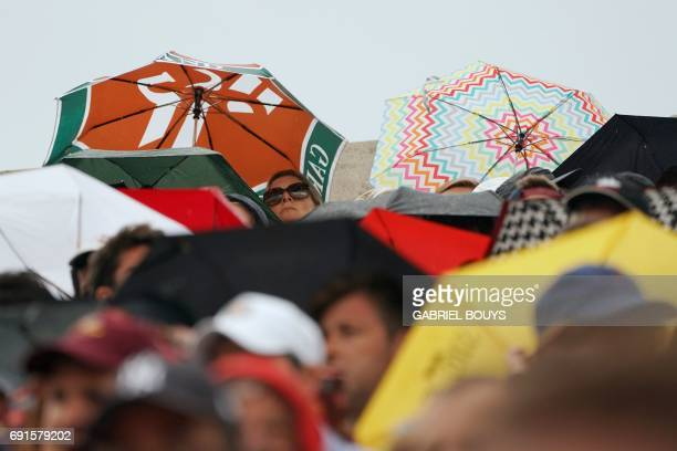 People sit with umbrellas under the rain as they watch the tennis match between Spain's Albert Ramos and France's Lucas Pouille on the Suzanne...