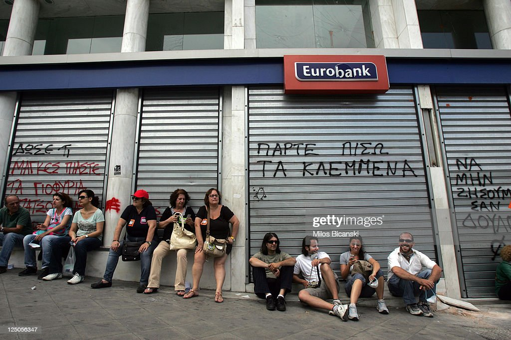 People sits in front of a Eurobank branch office in Athens on September 15, 2011 in Greece. As Greece's position in the Eurozone remains uncertain, a cabinet meeting today discussed how the country may implement a new round of austerity measures in order to fend off default and to ensure they continue to receive rescue loans. The troubled country is in its third year of recession and unemployment has risen to 16.3% compared with 11.8% this time last year.