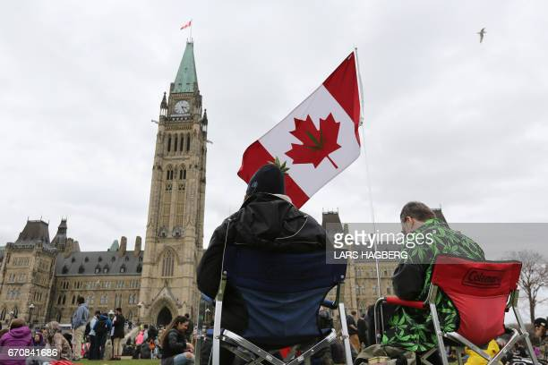 People sits on Parliament Hill waiting for the clock to hit 420pm on 4/20 in Ottawa Ontario April 20 2017 Polling released Thursday showed strong...