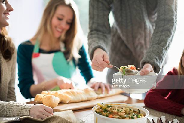 People sitting and standing at a table, a man serving food into a bowl, a woman slicing a baguette.