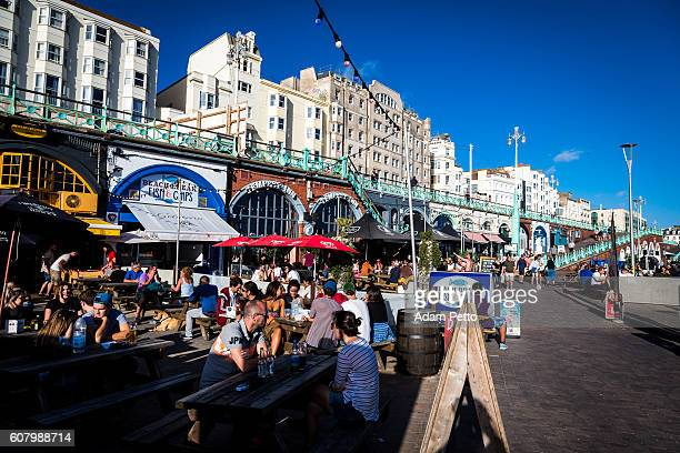 People sitting at picnic tables on seafront, Brighton, UK