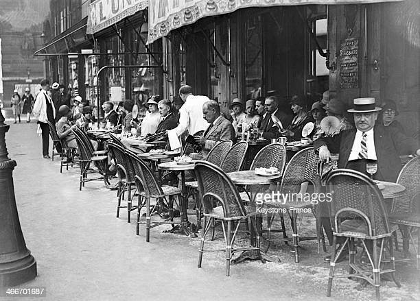 People sitting at sidewalk cafe during the heat wave in July 1929 in Paris France