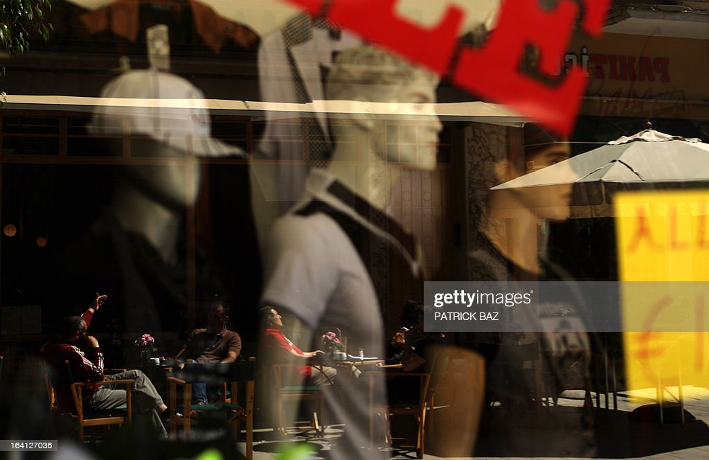 People sitting in a cafe are reflected on the window of a clothing shop window offering sales in Nicosia's Ledra street on March 20, 2013. Cyprus was scrambling to secure funding for its banks after lawmakers rejected the terms of a European Union bailout deal. AFP PHOTO / PATRICK BAZ