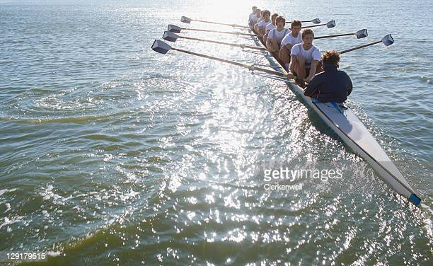 People sitting in a row oaring boat