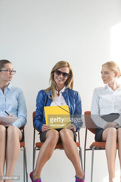 People sitting in a row, waiting for job interview