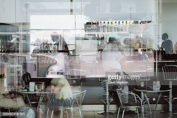 People sitting in cafe in airport, view through window