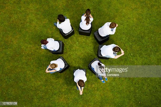 People sitting in circle in grass