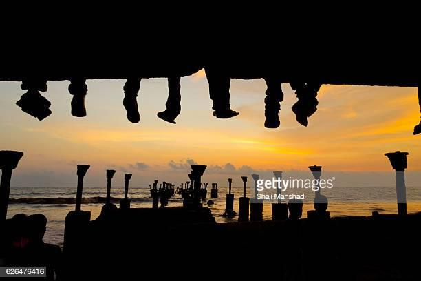 People sitting on a sea bridge hanging their legs at sunset