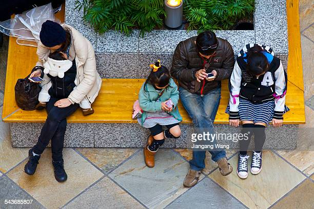 Kawasaki Kanagawa Prefecture Japan March 8 2015 People sitting on bench in a shopping mall are texting on their mobile phones