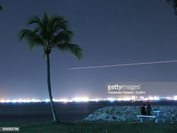 People Sitting On Bench Near Coconut Palm Tree At Riverbank Against Vapor Trail In Sky