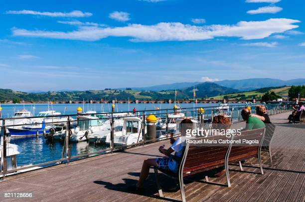 People sitting on public bench overlooking moored boats on the estuary