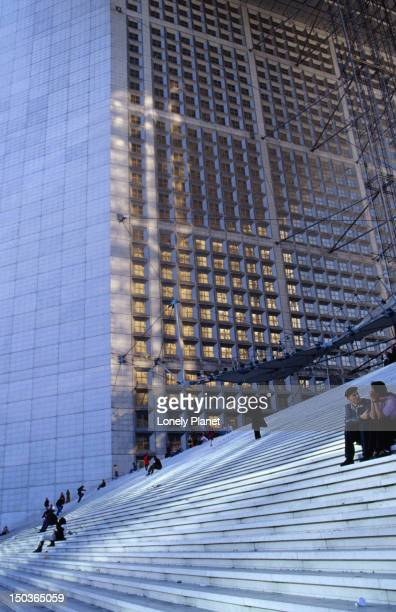 People sitting on steps of La Grande Arche in La Defense.