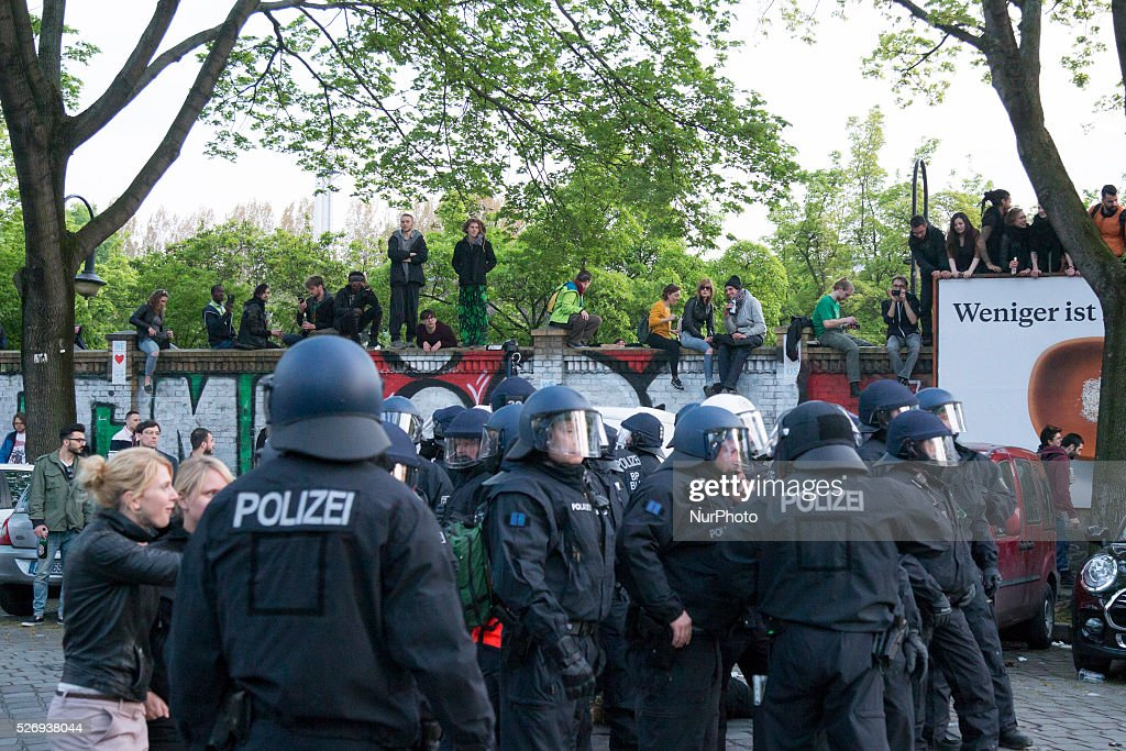 People sitting on the walls of Goerlitzer park observe the clashes between demonstrators and police in the Kreuzberg district on May 1, 2016 in Berlin, Germany. May Day, or International Workers' Day, was established as a public holiday in Germany in 1933. Since 1987 May Day has also become known in Berlin for violent clashes between police and mostly left-wing demonstrators.