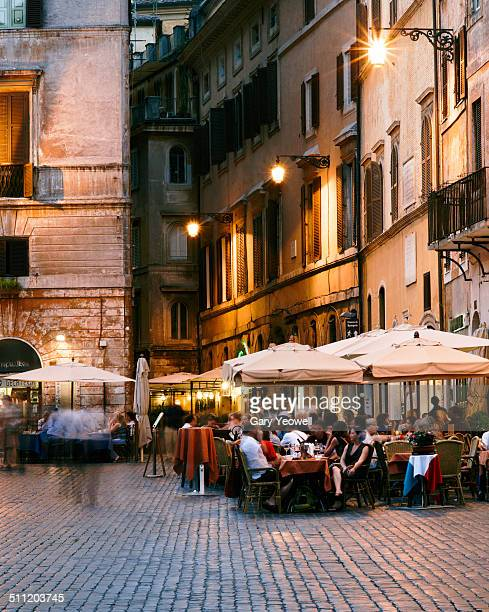 People sitting outside restaurants in a Piazza