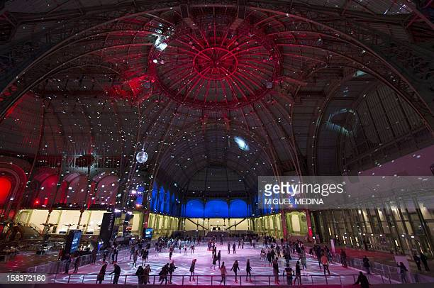 People skate at dusk on an ice rink hosted in the glassroofed central hall of the Grand Palais on December 14 in Paris At 1800 square metres in size...