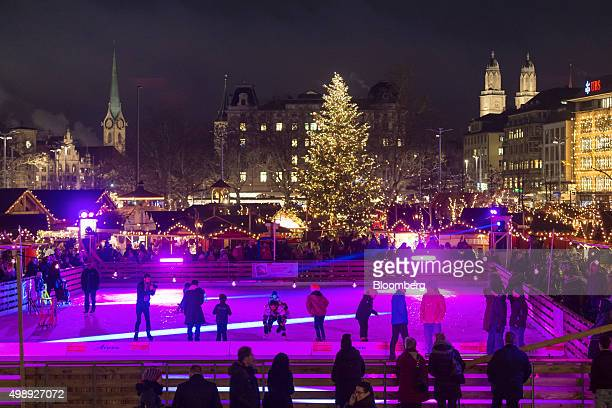 People skate on an ice rink as a Christmas tree and stalls stand illuminated at a Christmas market in front of the opera house in Zurich Switzerland...