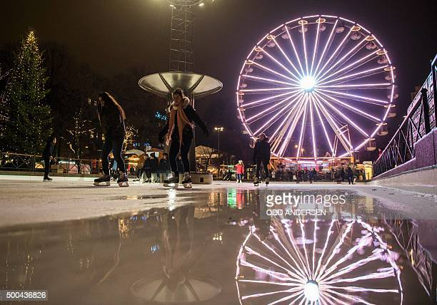 People skate past a puddle on an ice rink at a Christmas market in central Oslo on December 8 2015 The Norwegian capital has unusual warm weather...