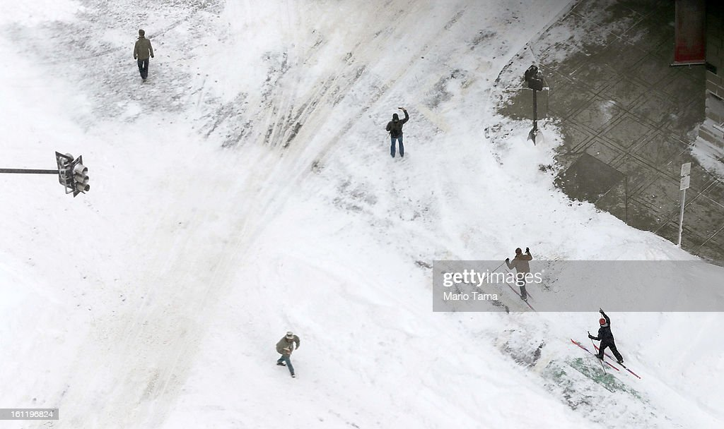 People ski as other stand on a street in the Back Bay neighborhood following a powerful blizzard on February 9, 2013 in Boston, Massachusetts. The storm knocked out power to 650,000 and dumped more than two feet of snow in parts of New England.