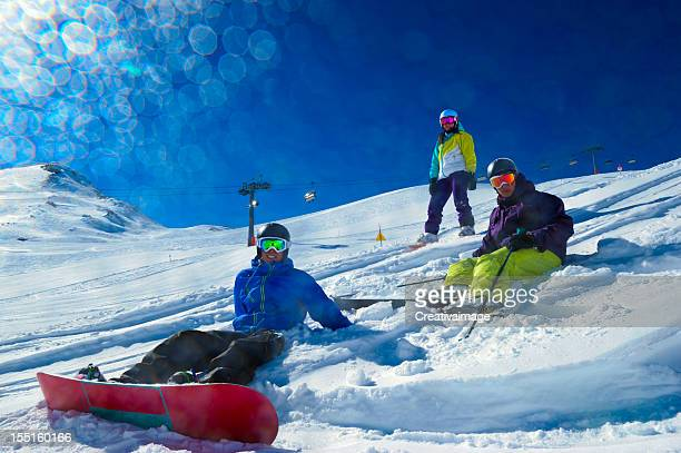 People skiing and snowboarding in powder snow